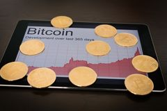 Bitcoins and rising chart on digital tablet Royalty Free Stock Image