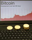 Bitcoins and rising chart on laptop computer Royalty Free Stock Photography