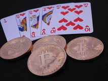 Bitcoins and royal flush. Four Bitcoins and royal flush in hearts on black background Royalty Free Stock Images