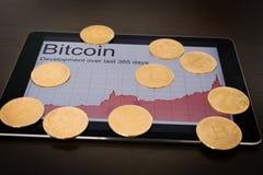 Bitcoins und steigendes Diagramm auf digitaler Tablette Lizenzfreies Stockbild