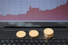 Bitcoins und steigendes Diagramm auf Laptop-Computer Lizenzfreie Stockfotografie