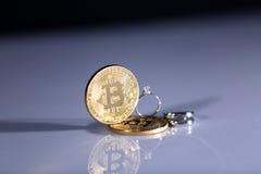 Bitcoins and wedding rings Royalty Free Stock Photos