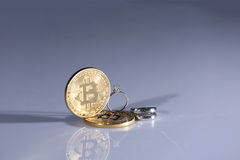 Bitcoins and wedding rings Royalty Free Stock Image
