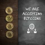 Bitcoins with chalkboard and the message `we are accepting bitcoins`. Bitcoins on wooden background with chalkboard and the message `we are accepting bitcoins stock photo