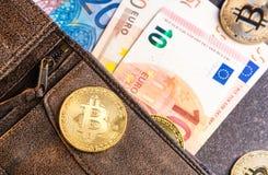 Bitcoins y billetes de banco euro en cartera Imagen de archivo libre de regalías