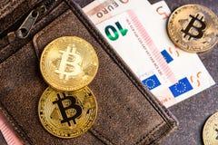 Bitcoins y billetes de banco euro en cartera Imagenes de archivo