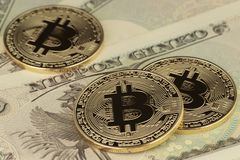 3 Bitcoins y moneda de los yenes fotos de archivo