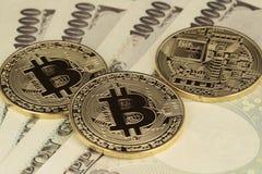 3 Bitcoins y moneda de los yenes fotografía de archivo libre de regalías