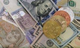 Bitcoins z USA banknotami i brytyjskimi banknotami, 20 funtów szterlingów, 10 funtowego szterlinga notatek złoty bitcoin, srebro obraz stock