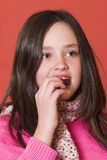 Bite. Young girl eating a chocolate Royalty Free Stock Photography