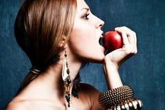 Bite an apple. Woman bite an apple, profile, studio shot stock images