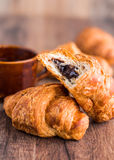 Bite chocolate croissant with a cup of coffee, french baking Royalty Free Stock Photos