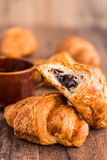Bite chocolate croissant with a cup of coffee, french baking Stock Photos