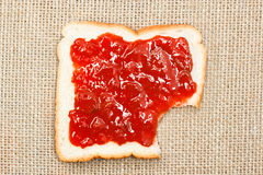 Bite out of a slice of bread with strawberry jam on sacking Stock Photography