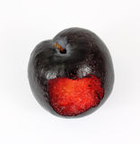Bite Ripe Plum. A bite into the juicy red flesh of a plum Stock Image