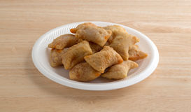 Bite size pepperoni pizza rolls on white foam plate. A serving of bite size pizza rolls on a white foam plate atop a wood table top illuminated with natural Stock Photography