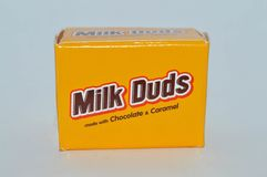 Bite size servings of chocolate Milk Duds in a yellow package. Bite size servings of yellow package of chocolate and caramel Milk Duds on a white background Stock Photography