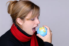 Bite The World. Attractive Young Woman Taking A Bite Out Of The World Stock Photography