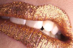 Bite your lip gold. Sexy lips biting lower lip with golden sparkle lipstick Stock Image