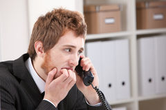 Bitebitebitebitebitebite on the phone bitebitebite nail-biting. Worried Young redheaded businessman nail-biting while listening to the phone royalty free stock images