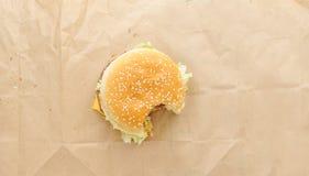biten av hamburgare på pappers- bakgrund Royaltyfri Fotografi