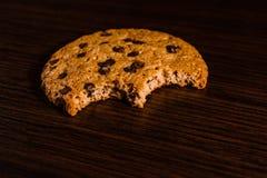 Biten choklad kaka på en mörk trätabell fotografering för bildbyråer