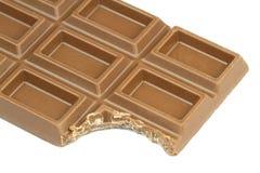Biten choklad på vit bakgrund arkivbild