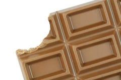 Biten choklad på vit bakgrund royaltyfri fotografi