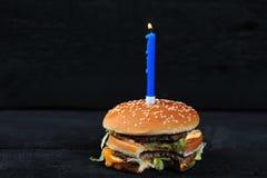 Biten hamburgare med en stearinljus med brand arkivbilder