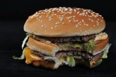 Biten hamburgare på ett lantligt mörker arkivbild