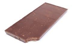 Biten mörk choklad på vit bakgrund royaltyfria foton