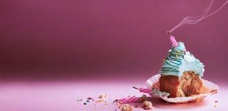 Biten muffin med kräm med släckta stearinljus Royaltyfri Fotografi