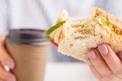 Biten ost- och grönsallatsmörgås i hand, hel smörgås royaltyfria bilder
