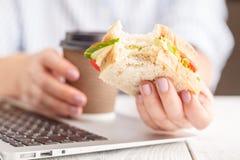 Biten ost- och grönsallatsmörgås i hand, hel smörgås arkivfoto