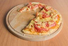 Biten skiva av en pizza royaltyfria foton