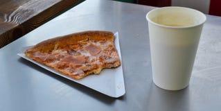 Biten skiva av pizza på en pappers- platta i ett kafé och en pappers- kopp kaffe arkivbild
