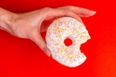 Biten smaklig vaniljmunk med stänk i kvinnas händer arkivfoton