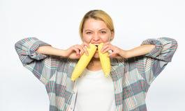Biter lantlig stil för flickan mogen havre Flicka som äter okokt och outredd mat Kvinnabonden äter på två gula havremajskolvar royaltyfri bild