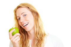 Biting in an apple. Happy blond woman eating a green apple royalty free stock images