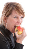 Biting in an apple. Pretty blond girl biting in an apple Royalty Free Stock Photo