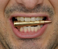 Biting on a bullet. An unshaved filthy tooth badass biting on a 5.56 mm M-16 bullet Royalty Free Stock Images