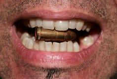 Biting a bullet. Image of biting a golden bullet Stock Image