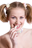 Biting the candy. Cute blond girl with ponytails biting in a candy Royalty Free Stock Images