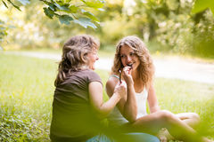 Biting chocolate. Mother and daughter enjoying leisure time. Royalty Free Stock Photo