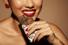 Biting dark chocolate Stock Photography