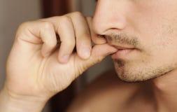 Biting fingernails. Young man biting his fingernails Royalty Free Stock Images
