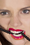 Biting her teeth on a string of beads. Beauty shot of a caucasian female with red, pink and orange lips biting on beads Royalty Free Stock Photography