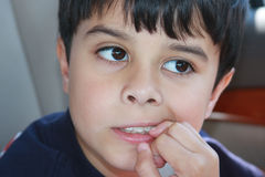 Biting Nails. Little boy biting nails, out of worry or bad habit Royalty Free Stock Photography