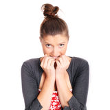 Biting nails. A portrait of a young frustrated woman biting her nails over white background royalty free stock photos