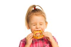 Biting the ring. Nice little girl biting bread ring isolated on white with closed eyes stock photography